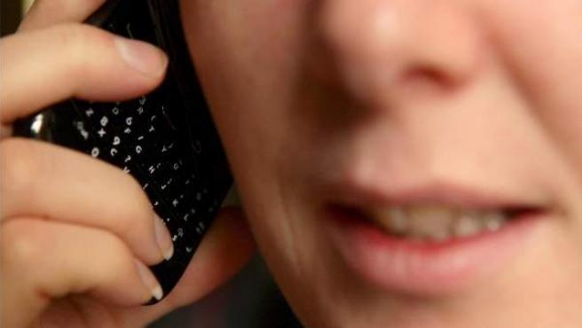 Una mujer, hablando por teléfono.