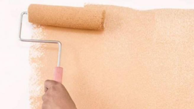 Dando color a la pared con un rodillo.