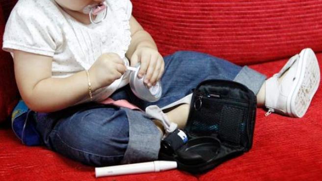 Un bebé de año y nueve meses con diabetes jugando con su glucómetro. El riesgo de hipoglucemias es mayor en los niños, ya que su cerebro se está formando y un correcto aporte de azúcar es imprescindible.