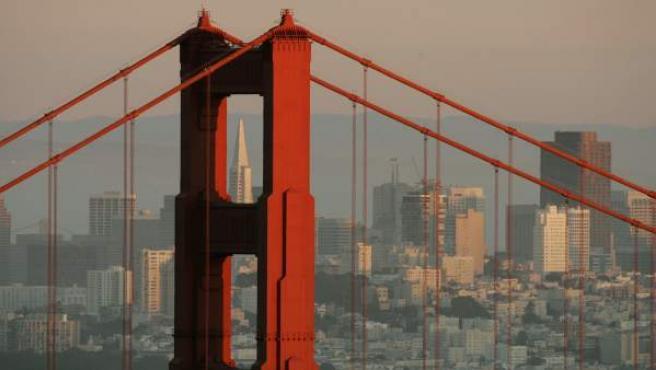 El sol se pone sobre la ciudad de San Francisco, con su puente más famosos, el Golden Gate, en primer plano.