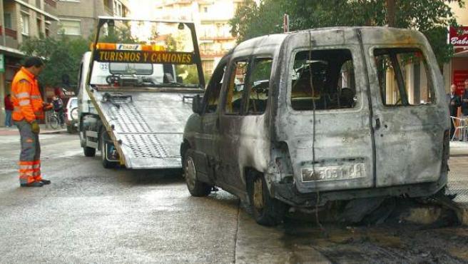 Una grúa se lleva un vehículo afectado por la quema de un contenedor en San José.