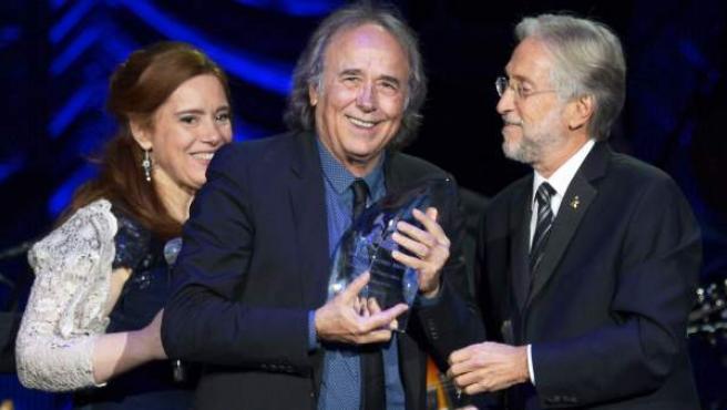 Joan Manuel Serrat recibe el premio a la Persona del Año por parte de la Academia Latina de la Grabación de manos de su presidente, Neil Portnow, y la presentadora de la ceremonia en su honor, Laura Tesoriero.