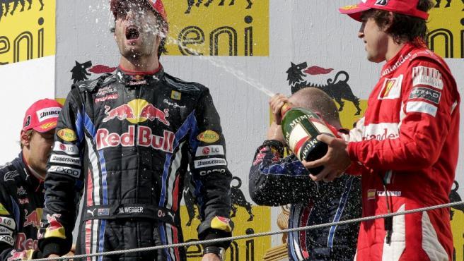 El piloto australiano Mark Webber (c) de la escudería Red Bull, el español Fernando Alonso (d) de la escudería Ferrari, y el alemán Sebastian Vettel (i) de Red Bull, celebran en el podio del Gran Premio de Hungría de Fórmula Uno en el circuito Hungaroring en Mogyorod, noreste de Budapest (Hungría).