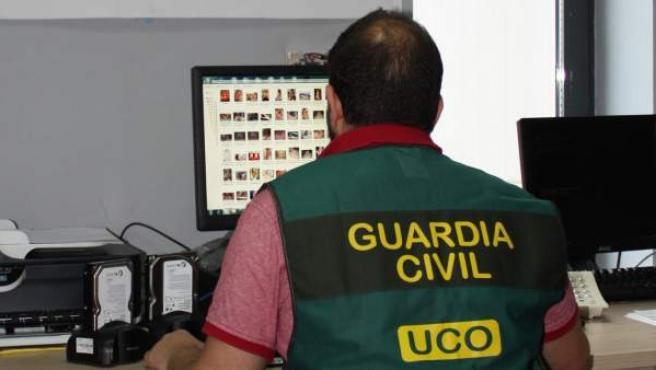 Un agente de la Guardia Civil, revisando los archivos descubiertos en una operación contra la pornografía infantil en Internet.