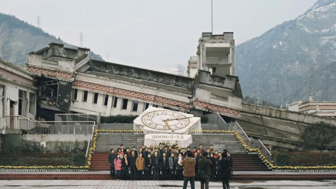 Turistas de un 'tour' posan ante un complejo educativo en el que murieron 300 estudiantes en el terremoto de Sichuan (China) de 2008