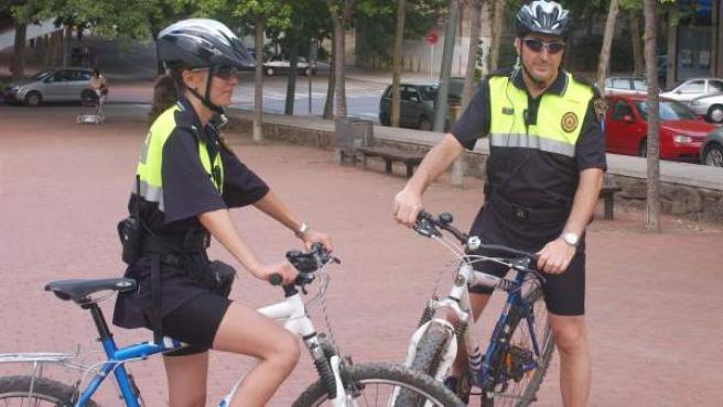 Dos agentes de la Policía Local de Barcelona posan junto a sus bicicletas.