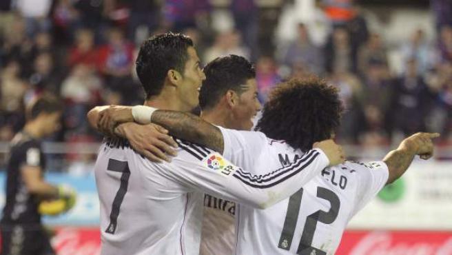 El delantero portugués del Real Madrid Cristiano Ronaldo (d) celebra con sus compañero James Rodríguez y Marcelo Vieira (d) el gol marcado al Eibar, segundo para el equipo, durante el partido de la duodécima jornada de Liga de Primera División disputado en el estadio de Ipurua.