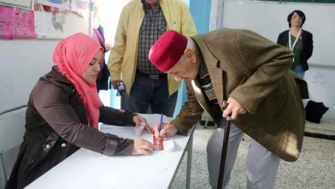Un anciano firma tras votar en la primera vuelta de las elecciones presidenciales en Túnez.