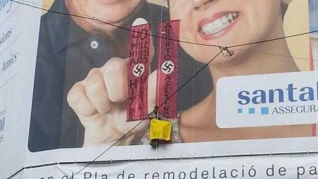 """Un hombre se ha colgado en la Pedrera y ha desplegados dos pancartas rojas con una esvástica en la que se puede leer """"aborto asesino"""" y """"40 mill niños año, Hitler novato""""."""