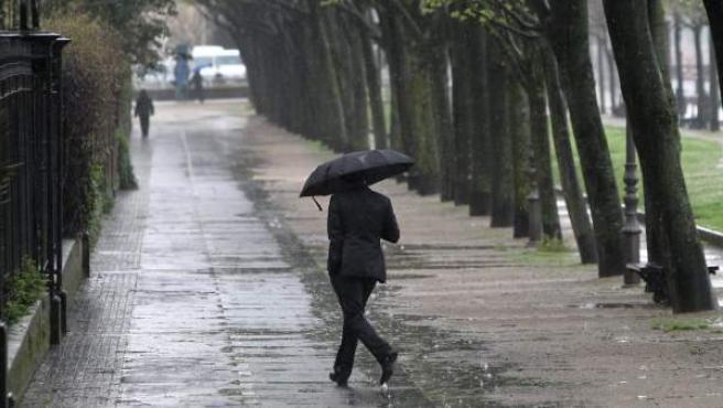 Un hombre se protege con un paraguas del fuerte viento y las lluvias en San Sebastián.