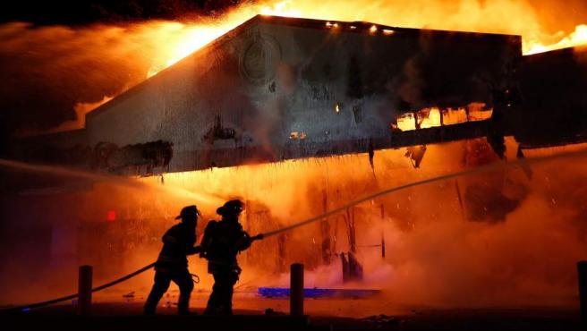 Unos bomberos intentan apagar el fuego en un establecimiento comercial de Ferguson (EE UU).