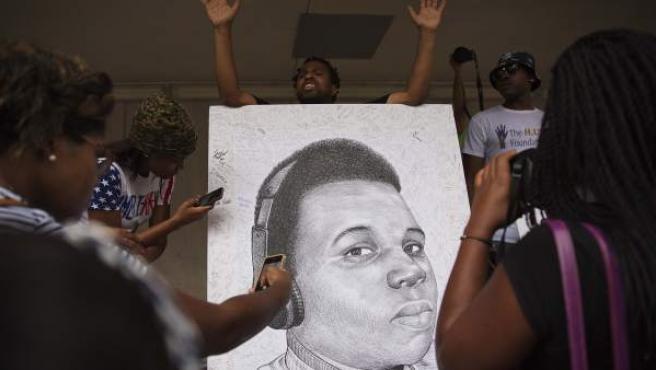Un grupo de manifestantes sujetan un retrato de Michael Brown.