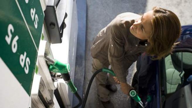 Una mujer echa gasolina a su coche.