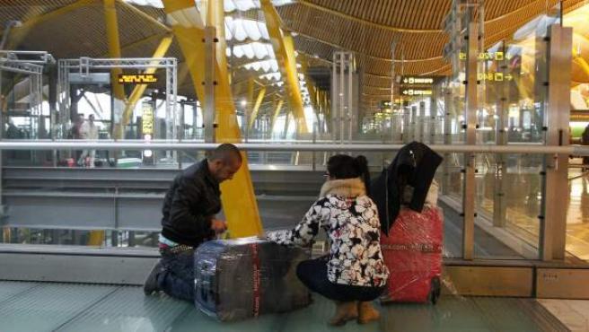 Un plastificador ilegal embala en plástico las maletas de una viajera en el aeropuerto de Barajas (Madrid).