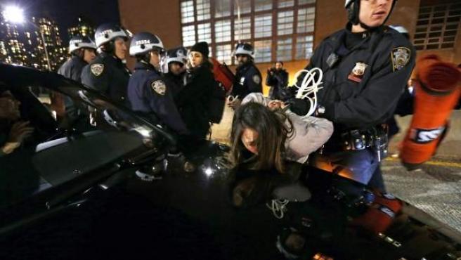 Policía arrestan a una joven durante una manifestación contra la decisión de no acusar formalmente a un policía que mató en julio pasado a un hombre negro.