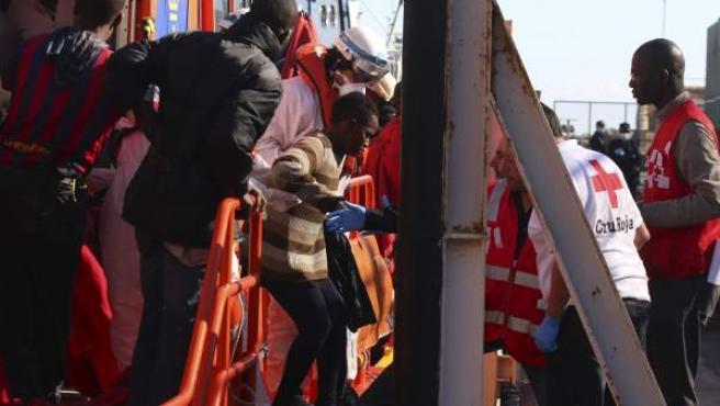 Varios de los 26 inmigrantes rescatados de la patera localizada este viernes en aguas del mar de Alborán, en la que también viajaban un bebé y una embarazada, a su llegada al puerto de Almería donde han sido atendidos por voluntarios de Cruz Roja