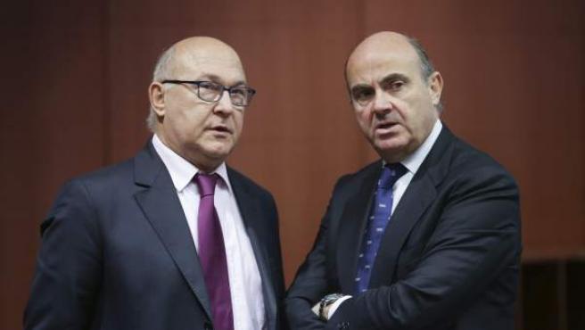 El ministro español de Economía y Competitividad, Luis de Guindos (d), charla con el ministro de Finanzas francés, Michel Sapin.