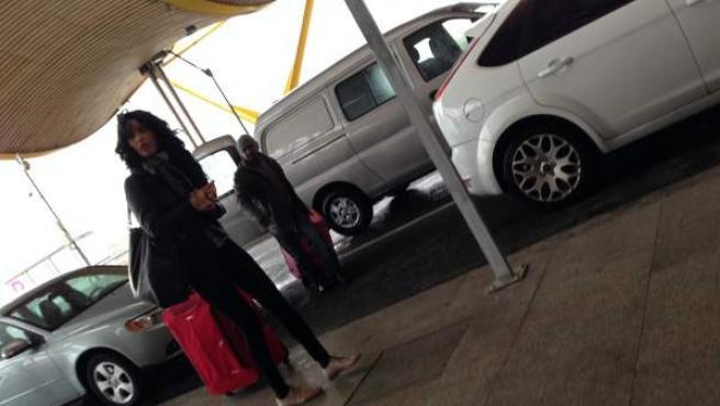 El conductor de un transporte ilegal ayuda a la pasajera que acaba de dejar en Barajas a poner sus maletas en un carrito en la Terminal 4.