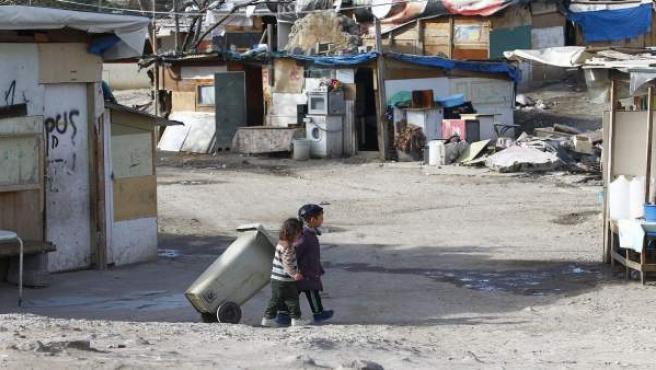 Dos niños jugando con un cubo de basura en el poblado de El Gallinero.