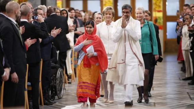La adolescente paquistaní Malala Yousafzai y el presidente de la Marcha Global contra el Trabajo Infantil, el indio Kailash Satyarthi, seguidos por miembros del Comité del Premio Nobel, a su llegada a la ceremonia de entrega del Premio Nobel de la Paz en el Ayuntamiento de Oslo (Noruega). Malala Yousafzai y Kailash Satyarthi reciben el Nobel de la Paz en el ayuntamiento de Oslo por su lucha por los derechos de los niños.