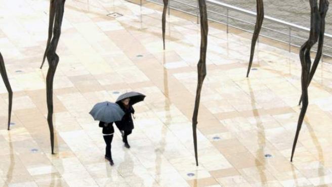 Dos personas pasean junto a la ría del Nervión de Bilbao, a su paso por el museo Guggenheim en una mañana lluviosa.