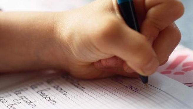 Un niño escribe a mano en un cuaderno.