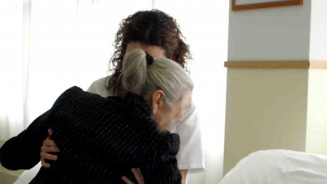 Una axuliar ayuda a una anciana.