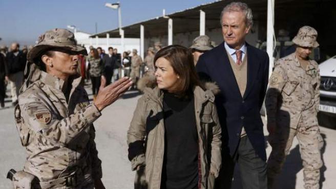 La vicepresidenta, Soraya Sáenz de Santamaría, acompañada por el ministro de Defensa, Pedro Morenés, atiende las explicaciones de un mando de la Base de Herat.