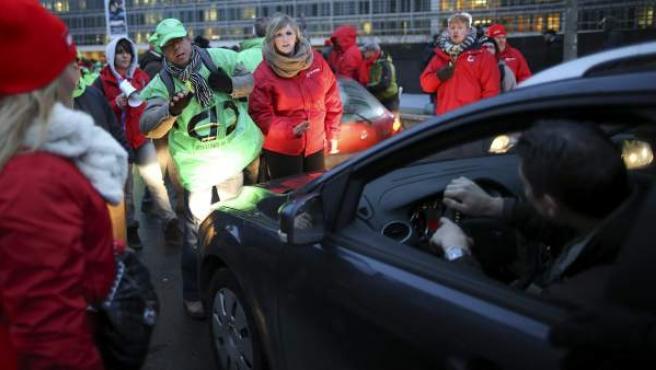 Representantes de sindicatos cortan el tráfico en la 'rue de la loi' en Bruselas durante la huelga general en protesta por las medidas económicas de austeridad del nuevo Gobierno liberal.