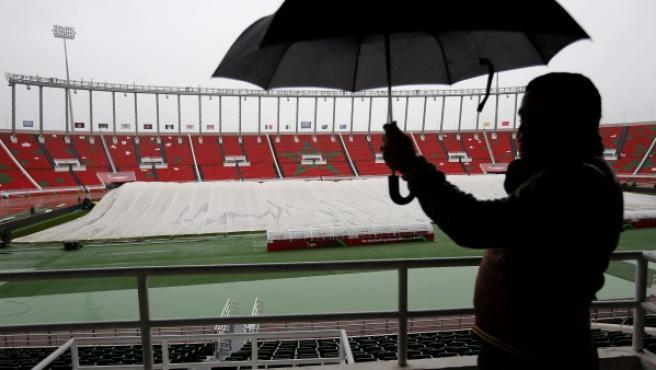 Operarios intentan proteger el césped del terreno de juego del estadio Moulay Abdellah de Rabat, encharcado tras las últimas lluvias.