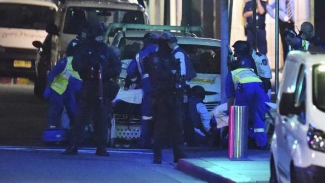 Miembros de los servicios médicos atienden a un herido junto a la cafetería tomada desde primeras horas de la mañana por un hombre armado en Sídney (Australia)