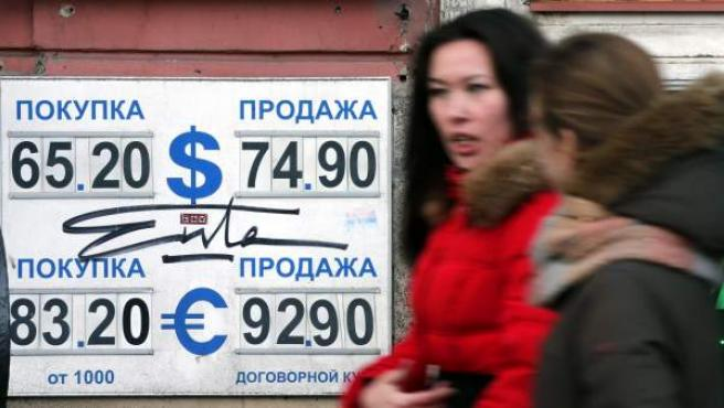 Dos mujeres pasan por delante de una oficina de cambio de divisas en Moscú, Rusia.