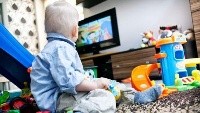 Un niño pequeño con sus juguetes y dibujos animados en la televisión.