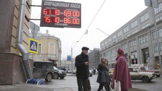 Dos transeúntes hablan ante un panel que muestra el cambio de divisas en Moscú.