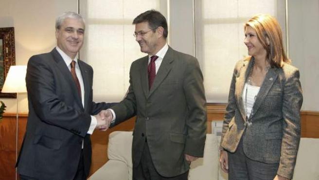 El consejero de Justicia, Germà Gordó, y el ministro del ramo, Rafael Catalá, se saludan en presencia de la delegada del Gobierno en Cataluña, María de los Llanos de Luna.