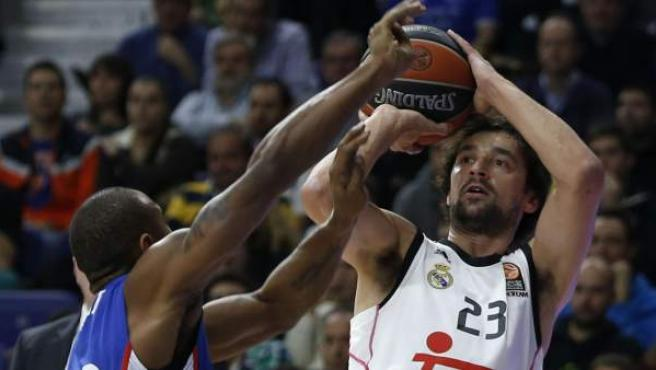 El base del Real Madrid Sergio Llull lanza a canasta ante el escolta del Aladolu Efes Dontaye Draper (i), durante el partido de la última jornada de la primera fase de la Euroliga que se juega hoy en el Palacio de los Deportes de Madrid.