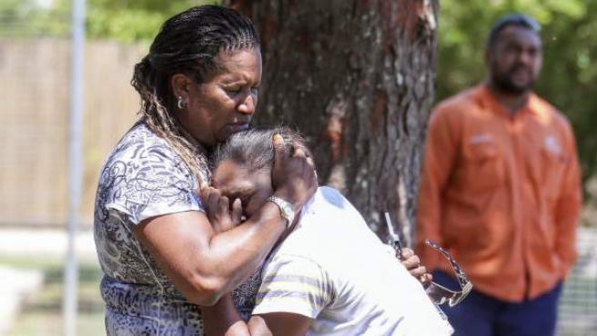 Dos mujeres lloran ante la vivienda en la que se han encontrado ocho niños, de entre 18 meses y 15 años, asesinados a puñaladas en la localidad de Cairns.