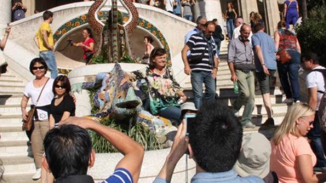 Varios turistas se fotografían junto al popular dragón de trencadís del Park Güell de Barcelona.