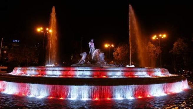 La fuente de Neptuno iluminada con los colores del Club Atlético de Madrid.