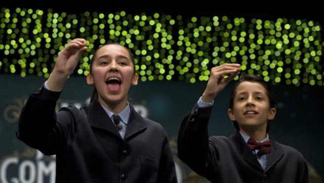 Los niños de San Ildefonso Ismael Rastrelli Mekerbech (d) y Janna Flores Villavicencio (i), han cantado el premio Gordo que ha recaído en el número 13.437, agraciado con 400.000 euros al décimo, en el sorteo extraordinario de la Lotería de Navidad.