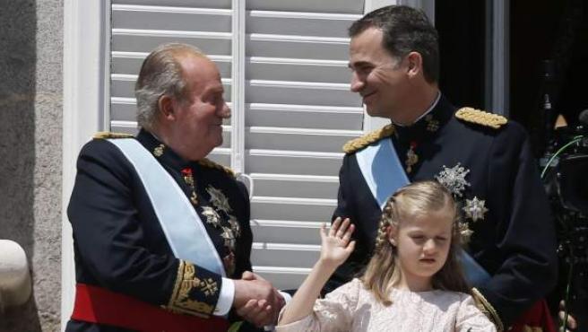 El Rey Felipe VI saluda a su padre, Don Juan Carlos, junto su hija la Princesa de Asturias Leonor, en el balcón central del Palacio Real, durante el día de su coronación.