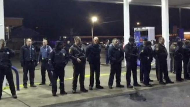 Captura de video que muestra a la policía formando un cordón de seguridad en la gasolinera donde un policía ha disparado y matado a un joven negro que iba armado en Berkeley, Misuri.