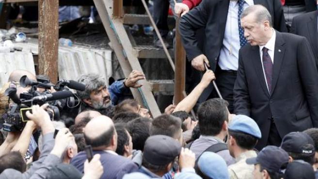 El primer ministro turco, Recep Tayyip Erdogan (dcha), abandona la mina de Soma tras visitar el lugar donde se produjo la explosión en la que murieron más de 200 mineros.