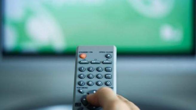 Una persona cambiando de canal con el mando a distancia.