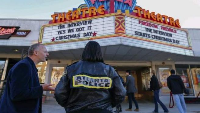 La policía observa la puerta de un cine mientras varias personas esperan para ver 'The Interview' en Atlanta.