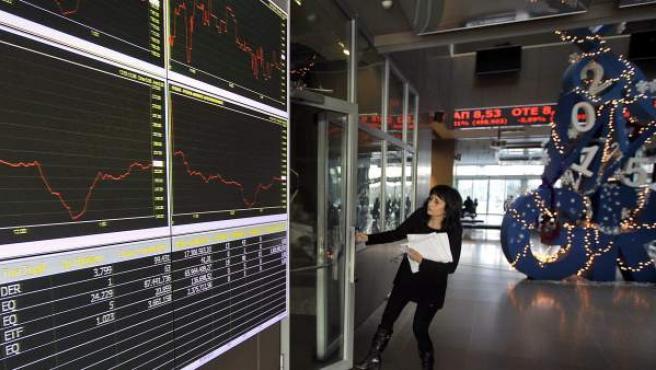 Una mujer pasa junto a unos paneles que muestran la información bursátil en Atenas (Grecia).