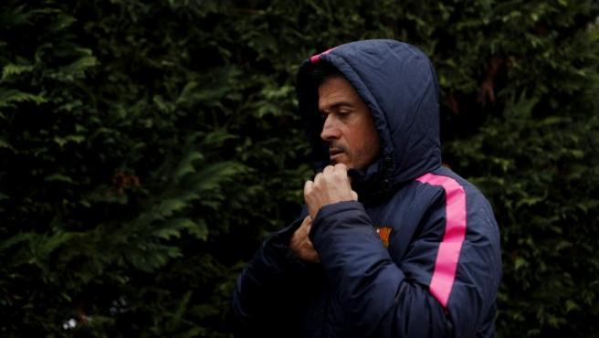 El asturiano Luis Enrique Martínez, entrenador del Barcelona, se protege de la lluvia mientras camina hacia la sala del prensa de la Ciudad Deportiva de la entidad culé.