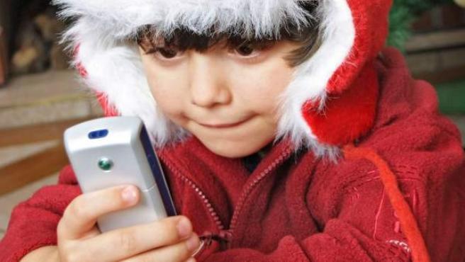 Un niño juega con el teléfono móvil que le han regalado por Navidad.