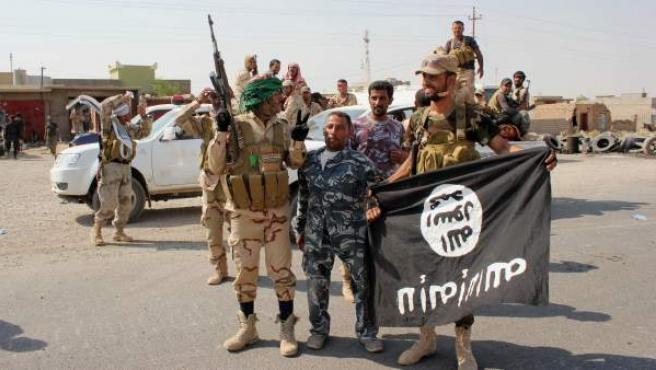 Milicianos chiíes sostienen una bandera del grupo Estado Islámico, durante una operación al norte de Bagdad, Irak.