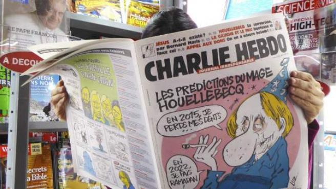 Una mujer lee el número del semanario satírico 'Charlie Hebdo', publicado antes del ataque terrorista, en un quiosco en París, Francia.